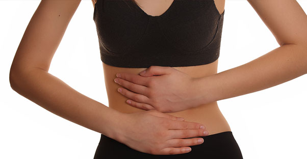a woman holds her stomach as it aches from IBS