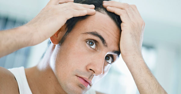 a man examines his hair line for hair loss