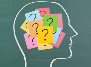 The outline of a head is drawn on a chalkboard, and the the brain area is covered in post-its with question marks on them.