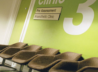 Empty tan chairs located in a green-walled doctors office that says Clinic 3 on the wall.