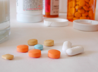 many containers of pills sit open showing pills for chrohns disease