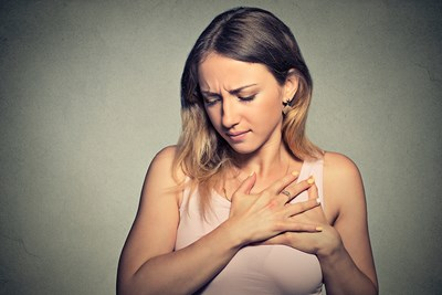 Woman holding her heart in pain
