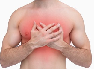 a man holds his chest in pain