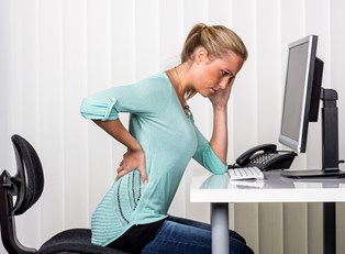 a woman has back pain while sitting at her desk in front of the computer