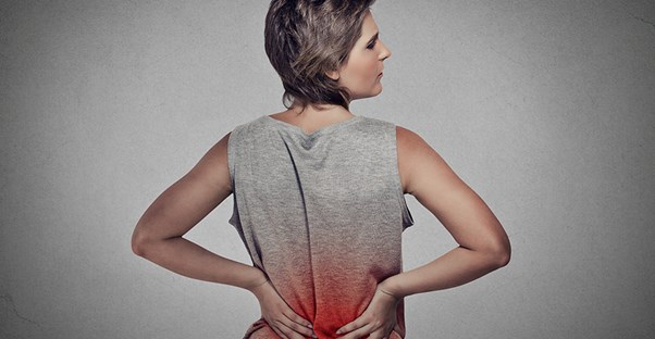 Woman in gray shirt experiencing back pain