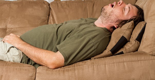 man snoring on couch