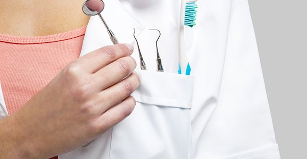 dentist holding tools to look at gingivitis symptoms