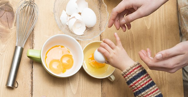 people reaching for raw eggs to represent who is at risk for salmonellosis