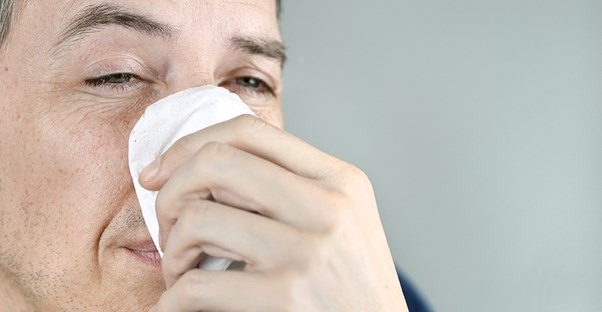 Man sneezing. Sinus infection causes.