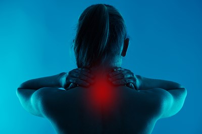 the neck of a woman glows red with chronic neck pain