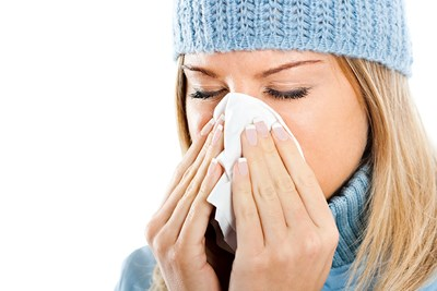 I woman blows her nose into a tissue.