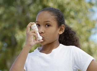 a young girl stops playing to use her inhaler for her asthma