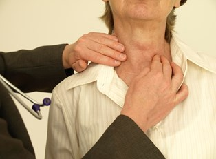 a doctor examines a patient for signs of hyperthyroidism