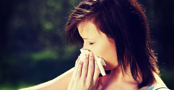 a woman with hay fever symptoms blows her nose