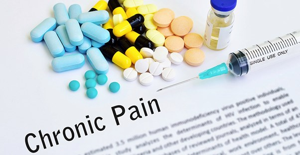 Pills and a syringe are gathered on top of a paper that has a description of chronic pain written on it.