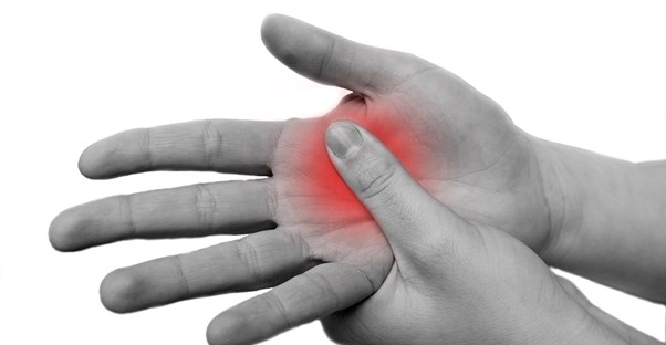 a blank and white hand swells in red pain from osteoarthritis