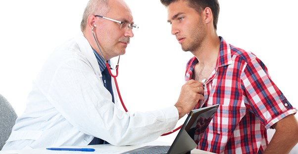 a doctor inspecting a patient for gynecomastia symptoms
