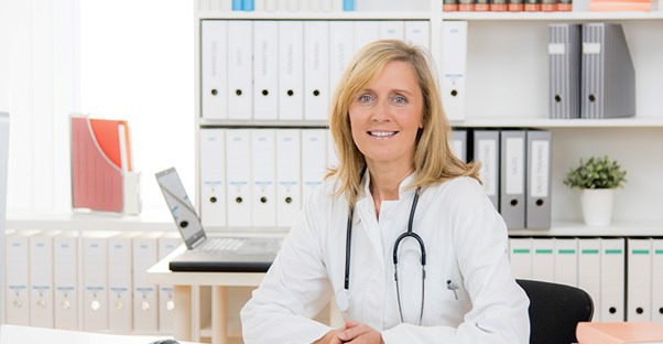 A doctor in a white lab coat sits in her office in front of a bookshelf of patient files.
