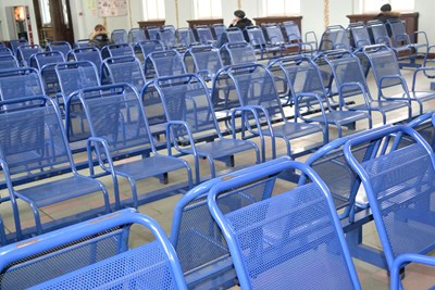 An array of empty blue chairs wait for patients to sit in them.