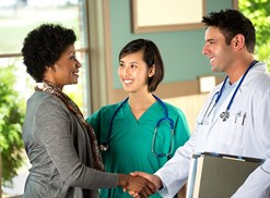 two health professionals greet a patient