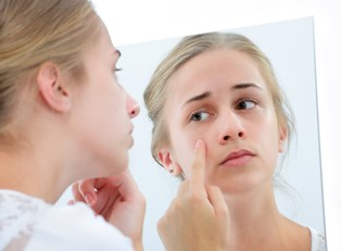 a woman who plans to discuss acne with her dermatologist