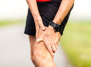 a runner grasps an area of knee pain