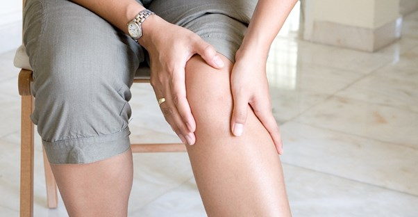 a woman hold an area of knee pain