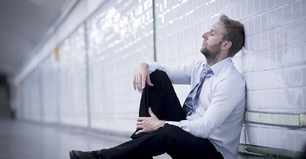 a man leans against a wall exasperated from his fibromyalgia pain