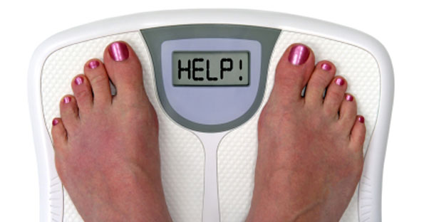 The feet of a person are visible on a digital scale that says the world HELP.