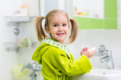 A young child practices skin care