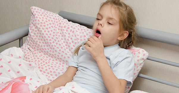child coughing in her bed