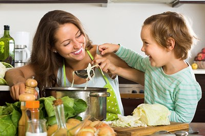 A woman and her child mix ingredients into a large cooking pot surrounded by vegetables, bread, and cheese on the counter.