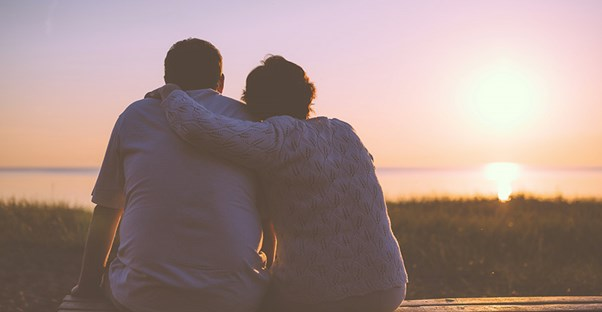 A couple has their arms over each others shoulders while sitting on a bench and watching the sun set in the distance.