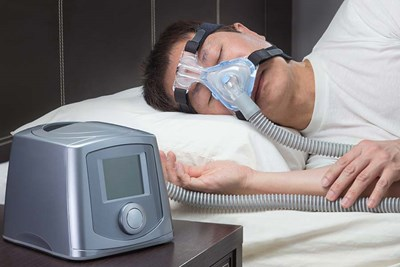 Man asleep wearing CPAP mask