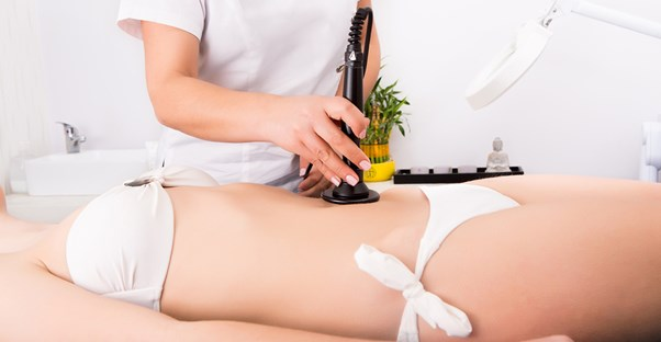 a woman getting her stretch marks vacuumed off her belly