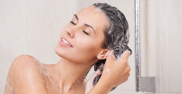 a woman fixing her oily hair with shampoo