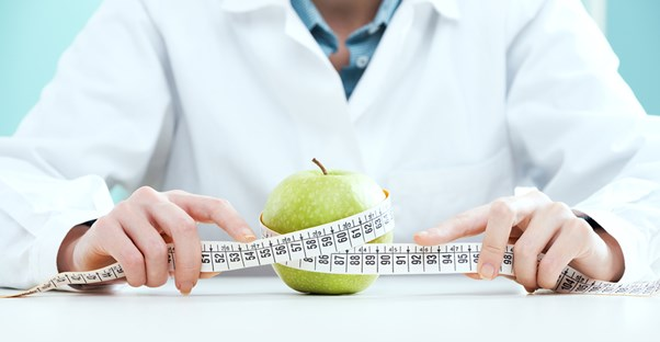 a nutritionist measuring an apple