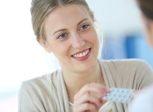 a woman picking up her oral contraceptives